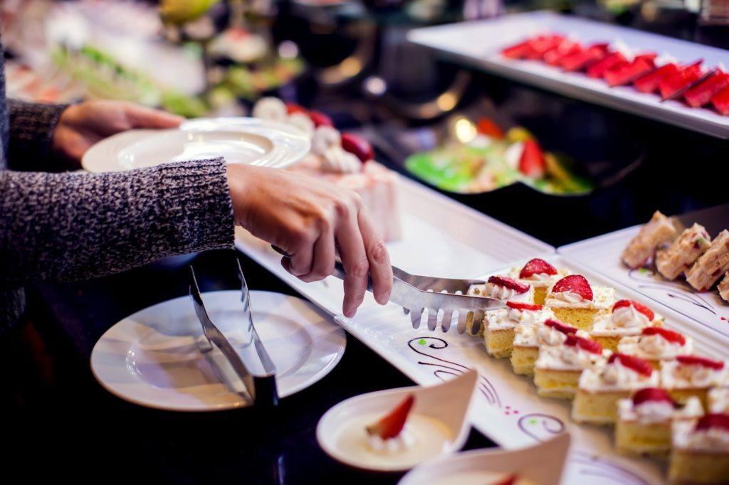 Tangan mengambil potongan cake menggunakan ala di tempat buffet.