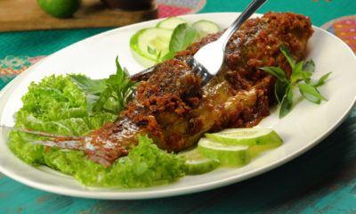Ikan bandeng bakar tengah dinikmati, tersaji di atas piring putih dengan sayur lalapan.