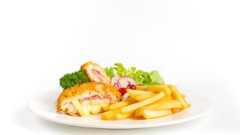 Chicken cordon bleu lengkap dengan kentang goreng dan sayuran tersaji di atas piring putih.