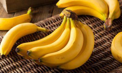 Satu sisir jenis pisang ambon dan beberapa buah pisang di belakangnya.