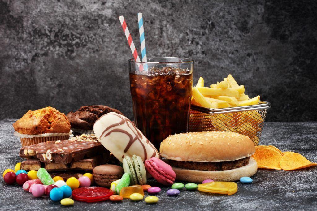 Sejumlah makanan fast food yang terdiri dari satu gelas cola, burger, donat, dan semangkuk kentang goreng.