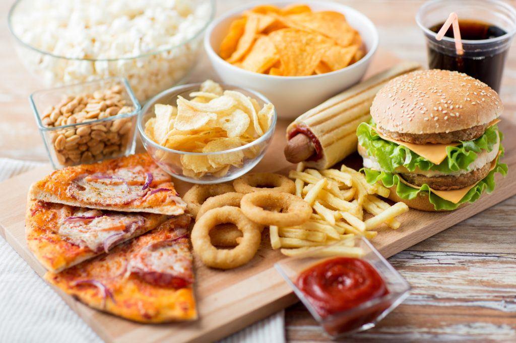 Satu papan kayu berisi potongan pizza, calamary, kentang goreng, keripik, dan burger.