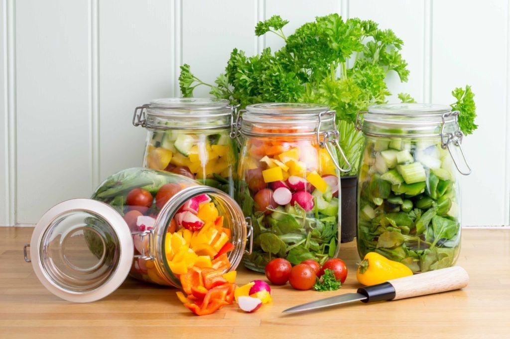 Empat mason jar besar berisi potongan sayuran, salah satunya terbuka.