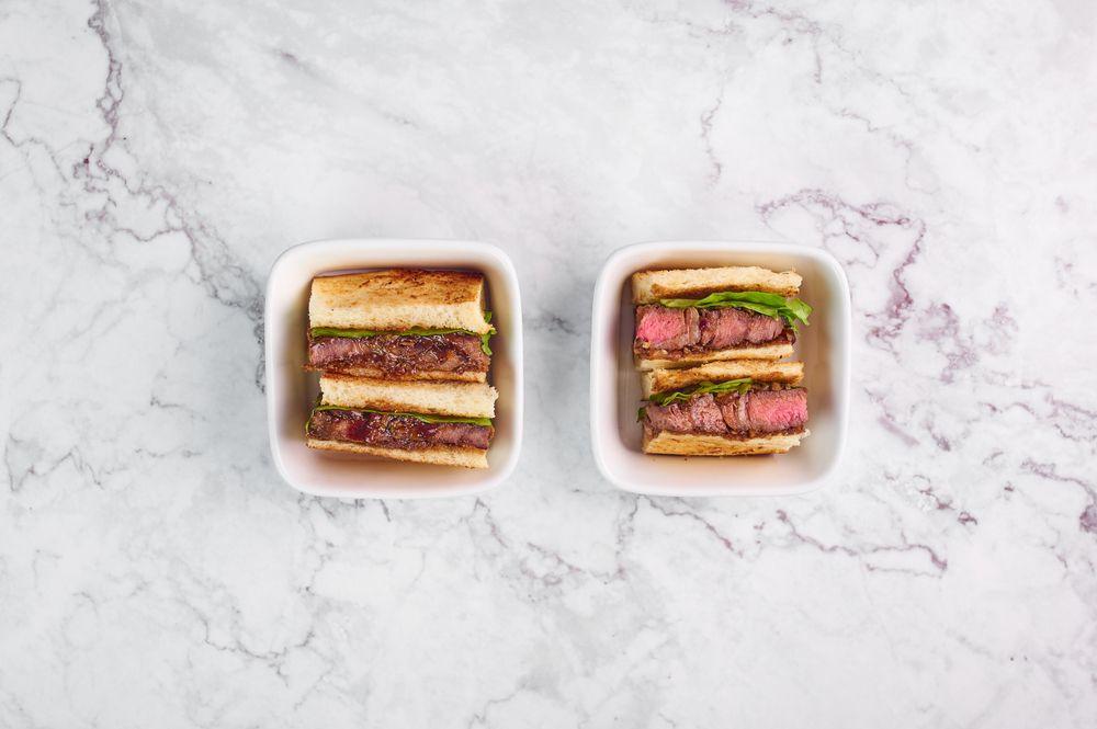 Roti sandwich Jepang dengan isian steak wagyu diletakkan pada dua mangkuk di atas meja marmer.