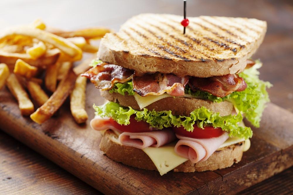 Roti sandwich dengan isian beef bacon, turkey, dan sayuran serta kentang goreng.