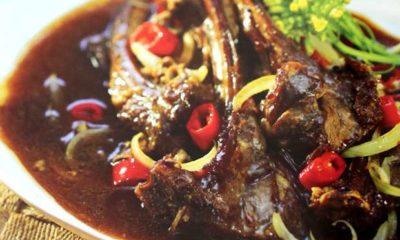 Semur daging kambing bagian iga tersaji di atas piring.