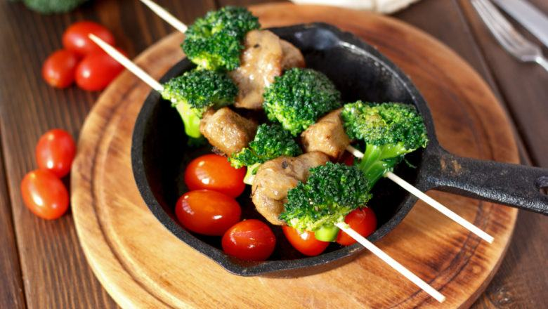 Hasil dari resep sate udang brokoli di atas panci baja hitam beralas meja kayu.