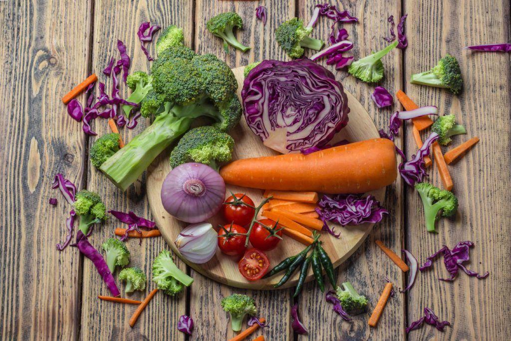 Satu talenan bulat kayu berisi bahan tumisan sayur berupa potongan wortel, kol ungu, tomat, bawang merah besar, dan brokoli.
