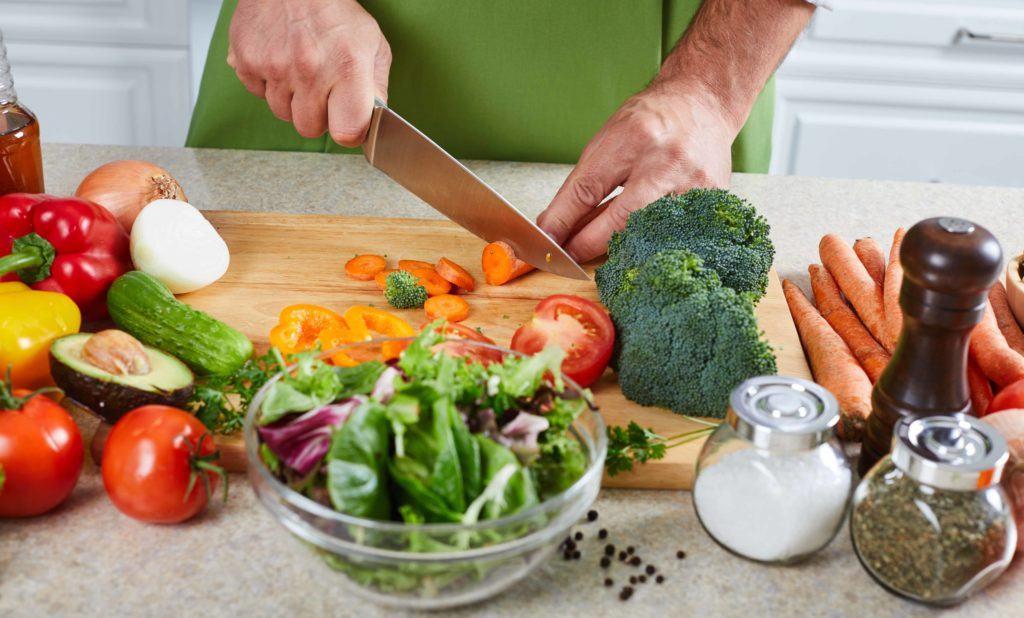 Tangan pria memotong wortel di atas talenan kayu dan di mejanya banyak sayuran