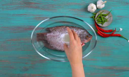 Ikan gurame dilumuri garam dalam piring kaca.