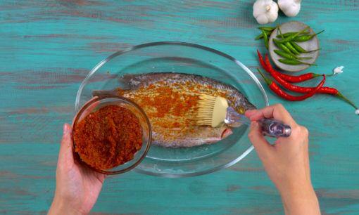 Ikan gurame dioleh bumbu merah menggunakan kuas.