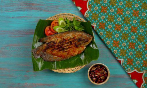 Ikan gurame bakar tersaji dengan lalapan dan sambal kecap.