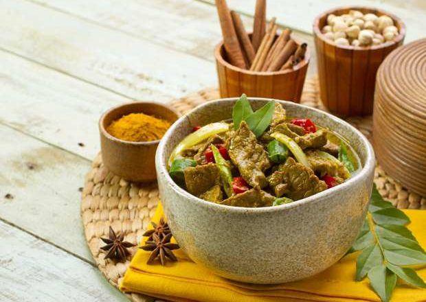 Daging masak kecap disajikan dalam mangkuk dan dikelilingi oleh rempah-rempah.