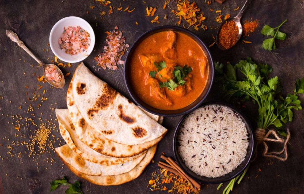 Masakan kari India disajikan dengan beberapa roti prata dan nasi.