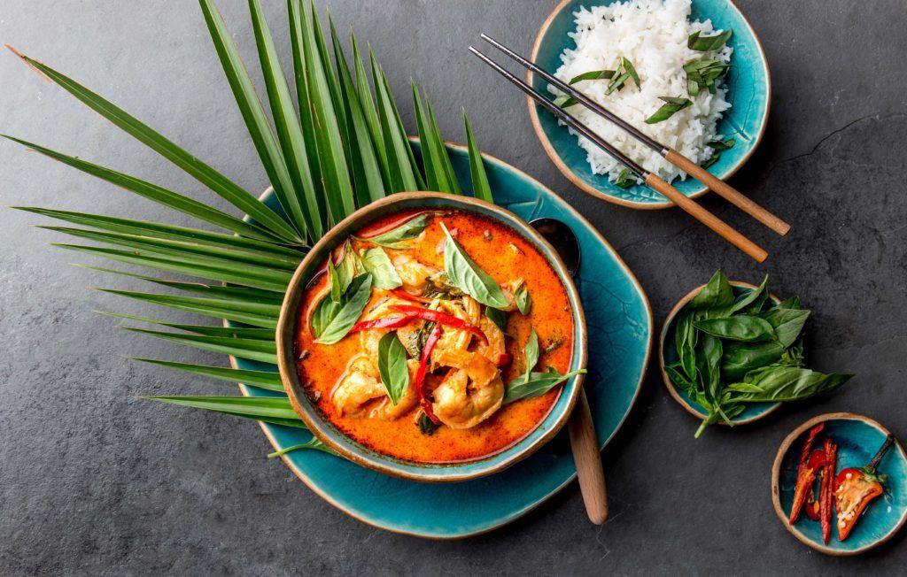 Semangkuk kari Thailand di atas piring hijau dengan daun pandan.