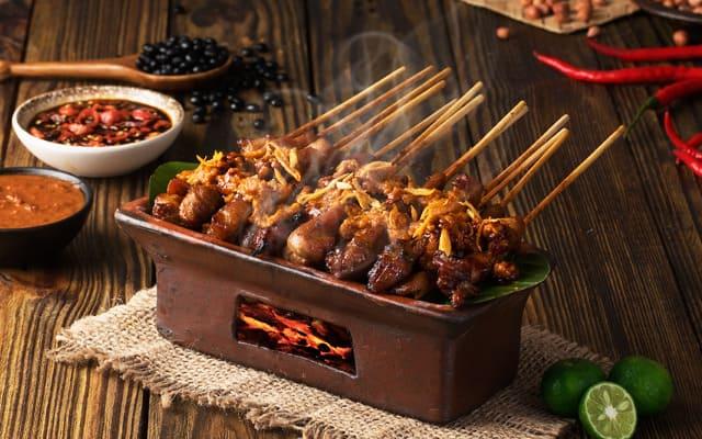 Sate ayam Ponorogo di atas pembakaran kecil dihidangkan di atas meja kayu.