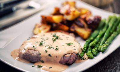 Piring berisikan steak, saus steak, asparagus, dan ubi.