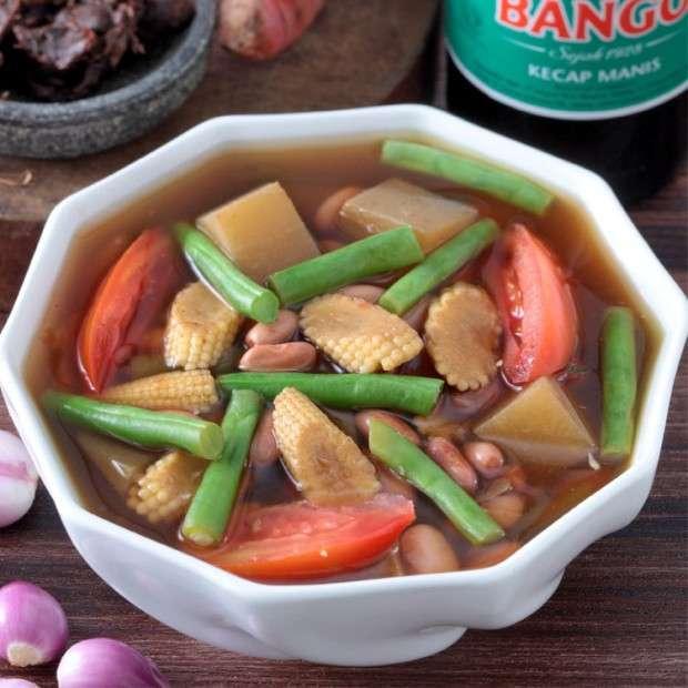 Semangkuk sayur asam kacang merah di atas meja makan kayu.