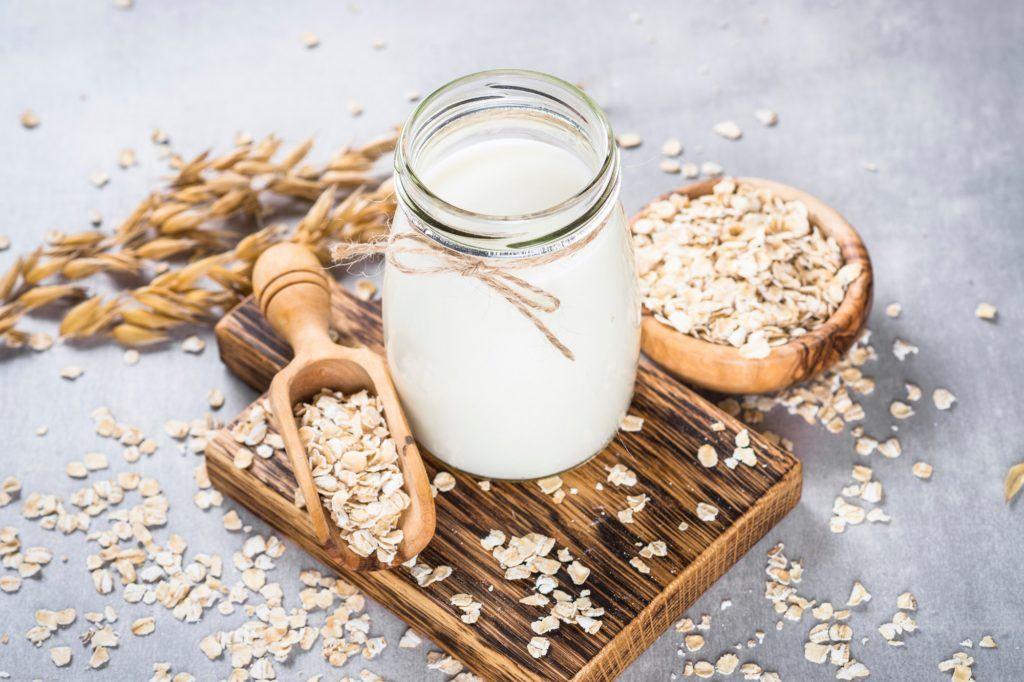 Susu gandum dalam botol kaca di atas tatakan kayu bertabur gandum.