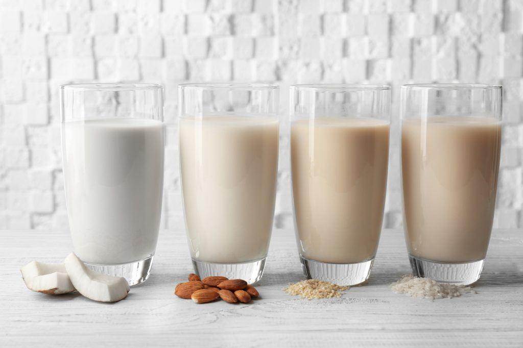 Empat gelas berisi susu kelapa, susu almond, susu oats, dan susu beras.