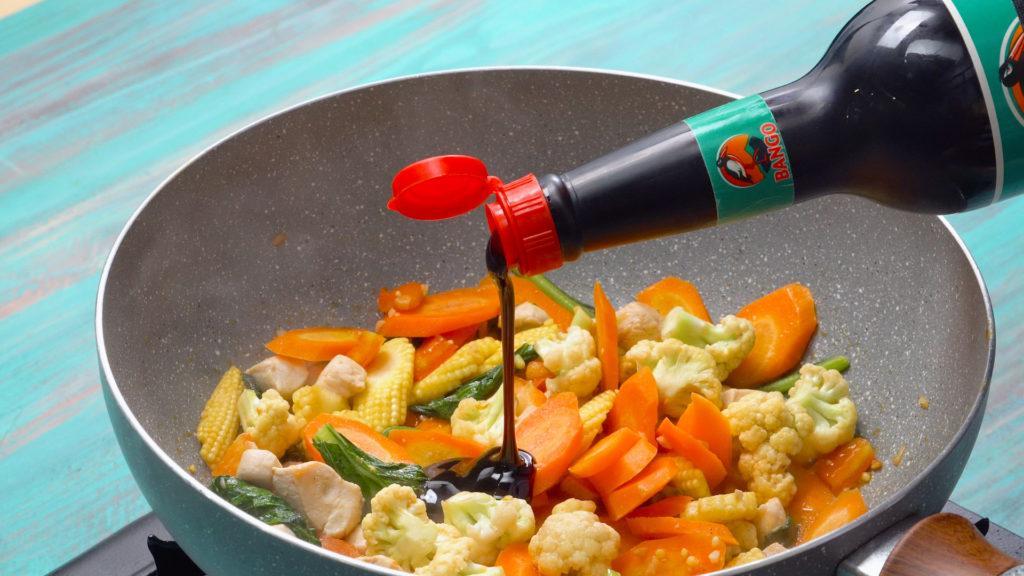 Kecap Bango dituangkan di atas irisan sayuran dalam wajan.