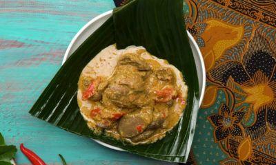 Hasil cara masak ati ampela kuah di atas piring beralas daun pisang.