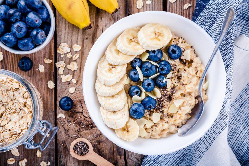 Satu mangkuk oatmeal bertabur blueberry dan potongan pisang.