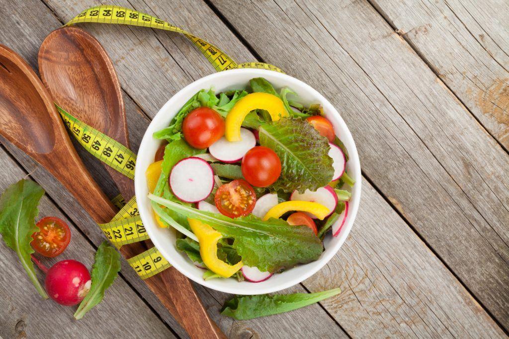 Diet kenyang dengan satu mangkuk sayuran dengan sendok kayu dan meteran pita di belakangnya.