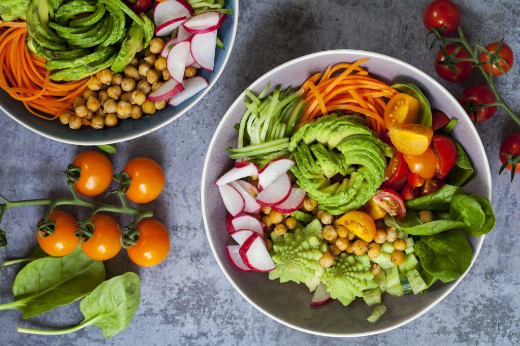 Satu mangkuk berisi raw food seperti potongan alpukat, bawang merah dan wortel.