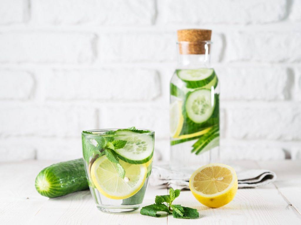 Resep Infused water untuk detox berupa lemon, mentimun, dan daun mint dalam gelas mening, dengan latas botol bening berisi infused water yang sama.