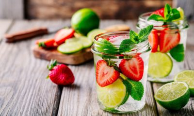 Dua glass jar berisi infused water stroberi, jeruk nipis, dan daun mint, dengan potongan buah di belakangnya.