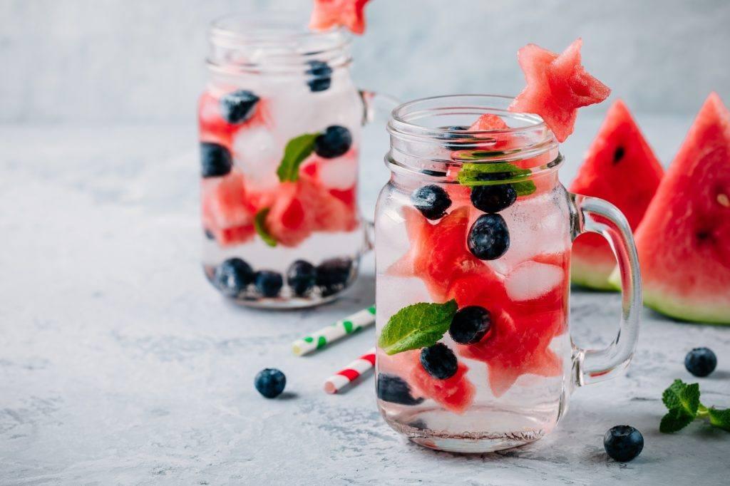 Dua gelas kaca berisi infused water semangka, blueberry, dan daun mint.