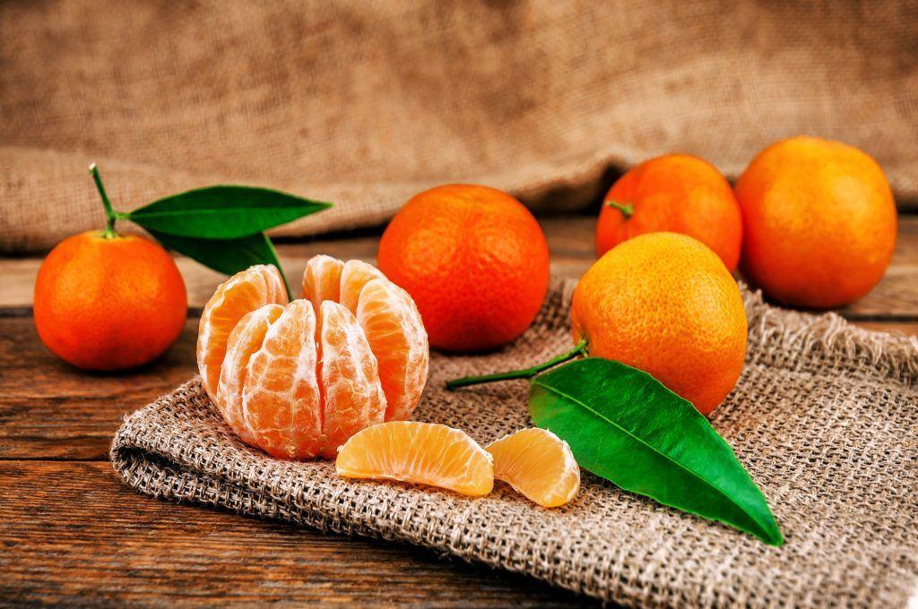 Jenis jeruk mandarin terkupas dan jeruk yang belum dikupas di belakangnya.