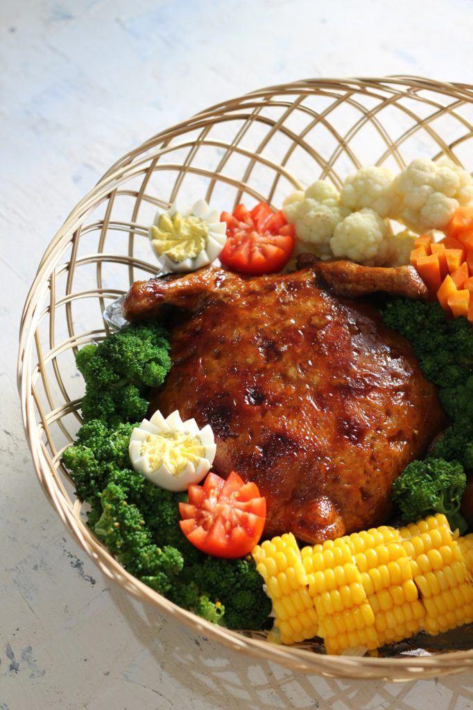 Ayam kodok di dalam keranjang bambu dihiasi garnish sayuran seperti jagung dan tomat.