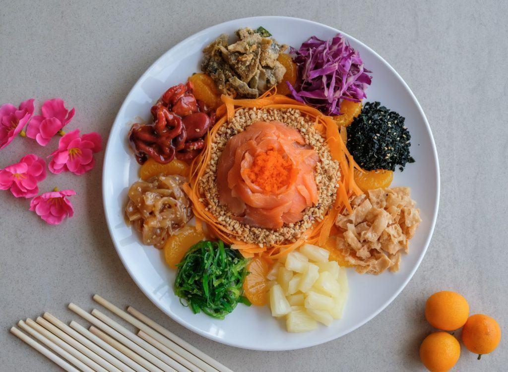 Satu piring yusheng dengan sumpit dan bunga di sampingnya.