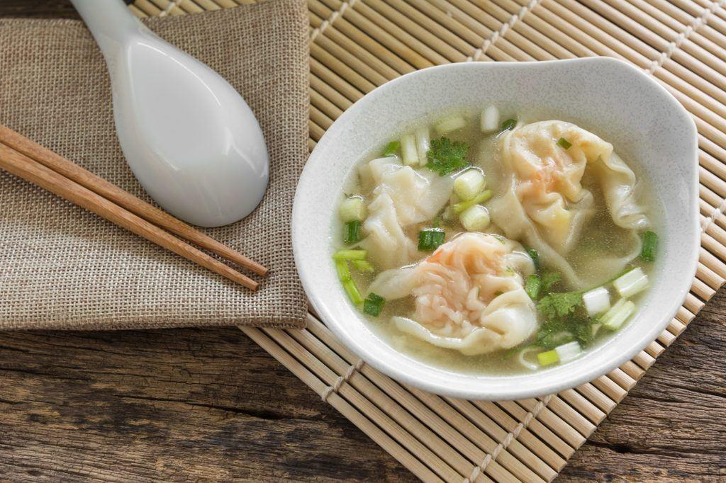 Mangkuk putih berisi wonton kuah, masakan khas Tionghoa, dengan sumpit dan sendok di sampingnya.