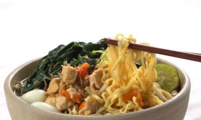 Semangkuk mie kangkung pedas tengah dinikmati dengan menggunakan sumpit.
