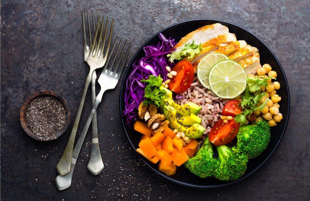 Satu piring hitam berisi makanan sehat dengan garpu di sampingnya.