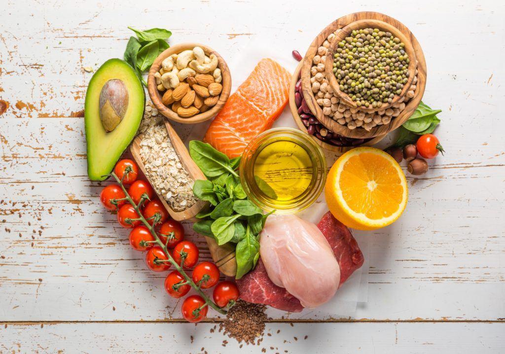 Makanan sehat dalam kondisi mentah seperti salmon, kacang-kacangan, dan alpukat dibentuk hati.