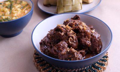 Satu mangkuk bumbu semur daging di belakangnya ada ketupat dan sayur nangka.