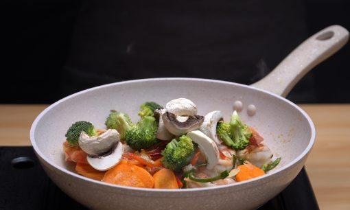 Aneka potongan sayur ditumis dalam wajan keramik.