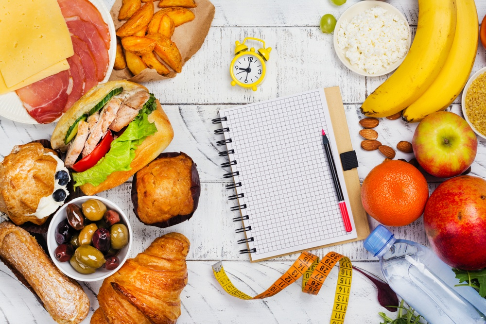 Jam waker di tengah makanan mentah yaitu salmon, alpukat, dada ayam, alpukat, dan kacang-kacangan untuk diet tanpa olahraga.