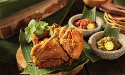 Ayam goreng kremes di atas daun pisang dan piring kayu dengan sambal di belakangnya.