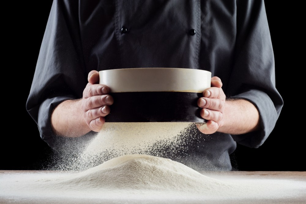 Seorang chef tengah menyaring tepung terigu untuk membuat kue menggunakan sieve, sebuah nama peralatan dapur yang unik.