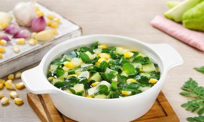 Sayur daun kelor bening tersaji dalam mangkuk putih di atas meja.