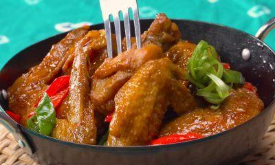 Hasil memasak resep sayap ayam pedas manis tersaji di atas piring hitam.