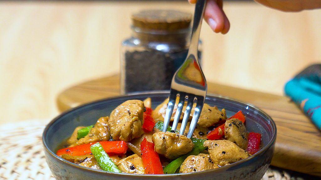 Seseorang tengah menikmati hasil masak resep ayam lada hitam yang tersaji di atas piring bersama tumisan paprika.