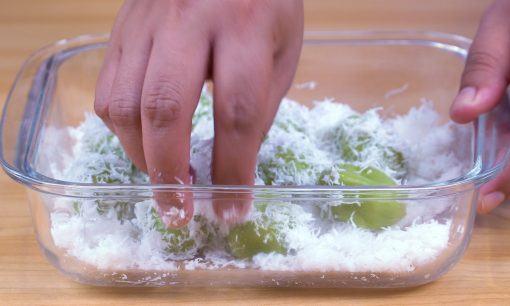 Tangan chef mengelimuti klepon dengan parutan kelapa.