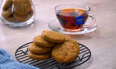 Hasil memanggang resep milk tea cookies tersaji bersama secangkir teh.