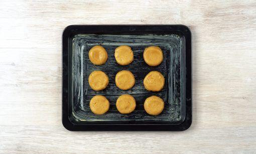 Adonan milk tea cookies yang telah dibentuk di dalam loyang kaca siap dioven